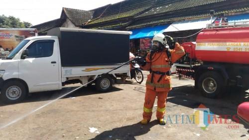 Salah satu petugas Pemadam Kebakaran Kota Batu menyemprot disinfektan di Pasar Besar Kota Batu, Jumat (20/3/2020). (Foto: Irsya Richa/MalangTIMES)