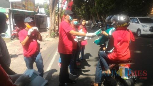 Suasana pembagian masker dan minuman kesehatan di depan Kantor PDI Perjuangan Banyuwangi. (Nurhadi Banyuwangi TIMES)