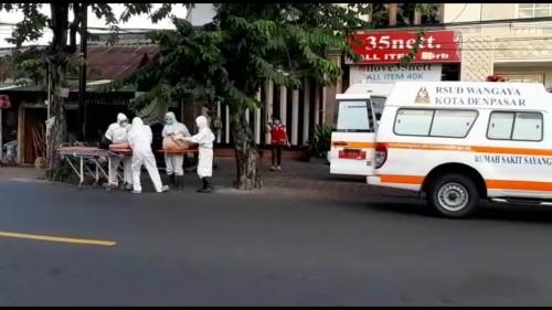 WNA yang tergelatak di pinggir jalan dan saat dilakukan evakuasi oleh petugas medis.