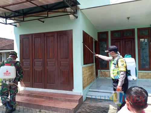 Babinkamtibmas, Babinsa dan perangkat Desa Slorok, Kromengan, saat melakukan penyemprotan disinfektan rumah warga, Rabu (25/3) (dd nana)