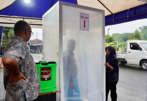 Salah satu masyarakat saat menjajal bilik disinfektan di Desa Sumbergondo Kecamatan Bumiaji. (Foto: istimewa)