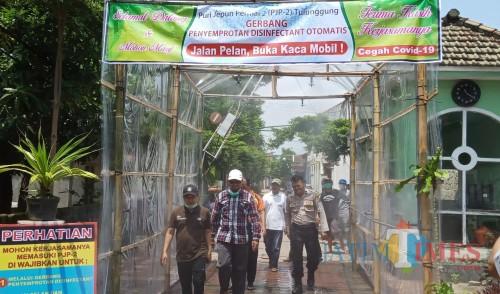 Warga melewati lorong Disinfektan di perumahan PJP 2 (Joko Pramono for Jatim Times)