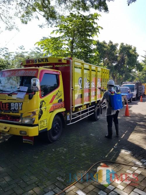 Para petugas Dishub Kabupaten Malang melakukan penyemprotan disinfektan ke kendaraan yang akan diuji kir. (dd nana)