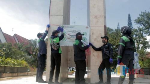 Pramu-taman saat melakukan pemasangan banner larangan masuk taman sementara di taman Jalan Ijen. (Igoy)