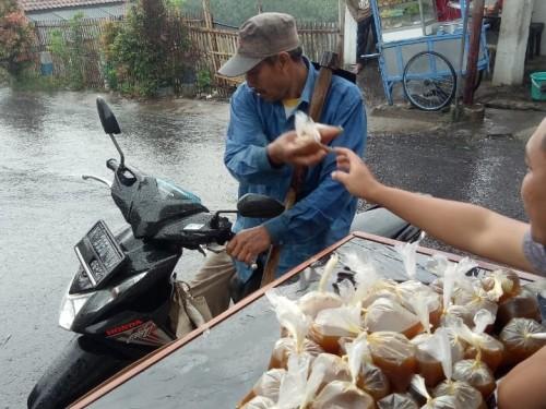 Salah satu anggota Karang Taruna saat membagikan jamu kepada masyarakat di Desa Sumbergondo, Kecamatan Bumiaji, Jumat (27/3/2020). (Foto: istimewa)