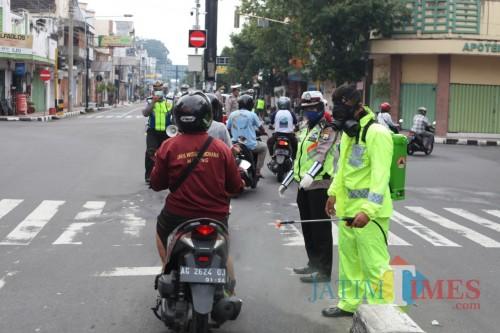 Para pengguna jalan disemprot disinfektan oleh Anggota Polres Blitar Kota.(Foto : Aunur Rofiq/BlitarTIMES)