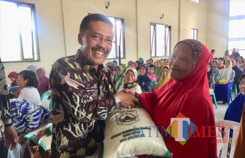 Wakil Wali Kota Batu Punjul Santoso saat memberikan bantuan beras kepada warga kurang mampu di Kota Batu beberapa saat lalu. (Foto: Irsya Richa/MalangTIMES)