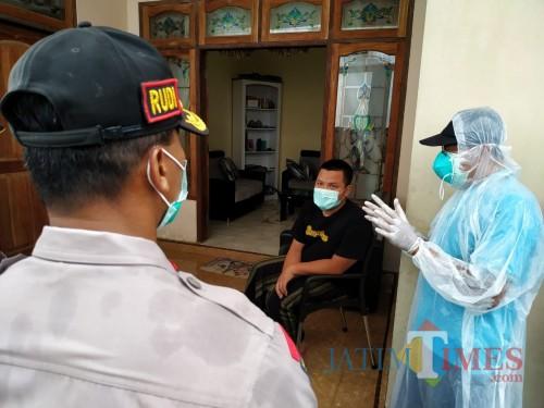 AH saat didatangi petugas dirumahnya untuk dijemput dan dipindah ke asrama rusunawa tempat Karantina / Foto : Anang Basso / Tulungagung TIMES