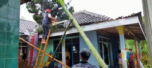 Petugas gabungan saat mengevakuasi pohon tumbang yang menimpa rumah salah satu warga (Foto : PMI Kabupaten Malang for MalangTIMES)