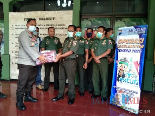 Kapolres Tulungagung,  AKBP Eva Guna Pandia saat serahkan bantuan masker pada Dandim Tulungagung. Letkol Inf. Kaharudin (foto: Joko Pramono/JatimTIMES)