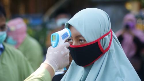 Salah satu santri diperiksa suhunya dengan thermo gun oleh tim kesehatan (Joko Pramono for JatimTIMES)