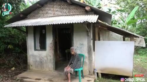 Kondisi Mbah Ginten yang sedang duduk di depan rumahnya, yang berada di pelosok perkampungan Desa Pakem, Kecamatan Wajak, Kabupaten Malang. (Foto: YouTube Cak Budi Official)