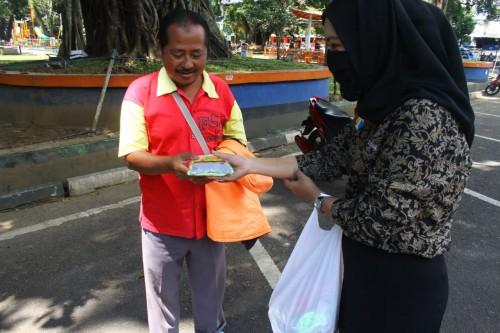 Pewarta Kodew Malang saat membagikan paket bantuan kepada pekerja di jalan yang masih berjuang di tengah pandemi covid-19. (Istimewa).