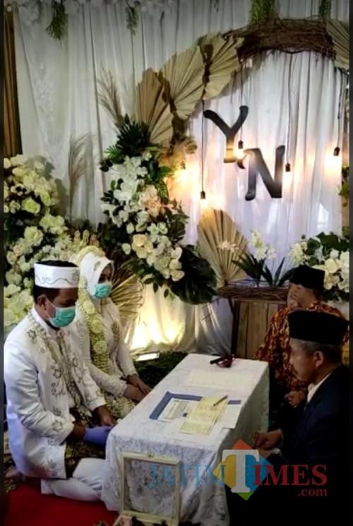 Yusuf dan Nikmah saat melangsungkan akad nikah dengan menggunakan masker penutup mulut serta sarung tangan medis. (Foto: Yusuf for MalangTimes)