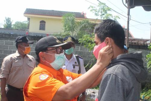 Bupati Blitar Rijanto memberikan dan memakaikan masker kepada pengendara yang singgah di check point Desa Gandekan Wonodadi.(Foto : Aunur Rofiq/BlitarTIMES)