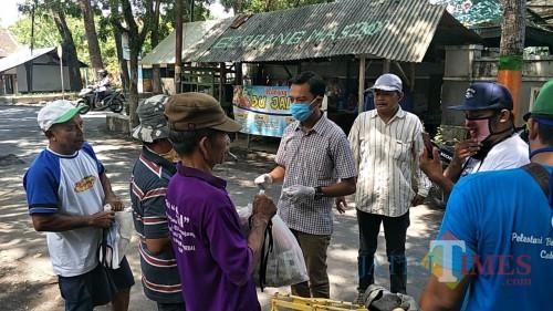 Ketua Paguyuban Kicau Mania ketika menyerahkan sembako kepada warga (Foto : Moch. R. Abdul Fatah / Jatim TIMES)