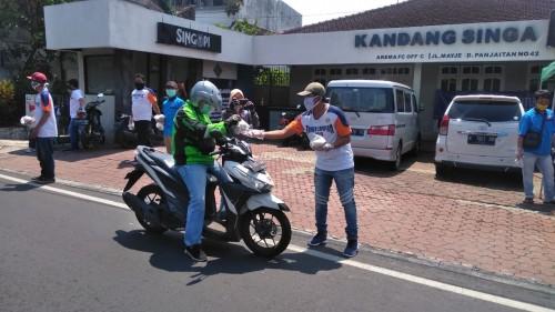 Karyawan Arema FC dan warga sekitar Jalan Mayjen Pandjaitan membagikan nasi bungkus kepada pekerja jalanan dan ojol (official Arema FC)