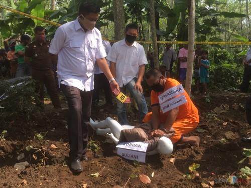 Tersangka Agus Widodo (jongkok) saat memperagakan adegan saat dirinya membunuh istrinya (Foto: Ashaq Lupito/ MalangTIMES)