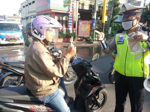 Petugas Dikyasa yang memberikan APD masker kepada pengendara tak bermasker (Ist)