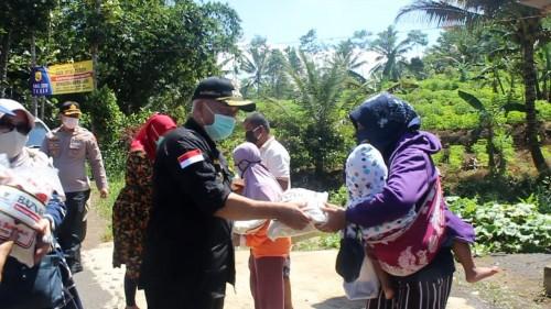 Bupati Malang H.M. Sanusi menyalurkan bantuan beras seberat lima kilogram kepada warga di Kecamatan Ampelgading, Kamis (23/4/2020). (Foto: Dok. Malang Times)