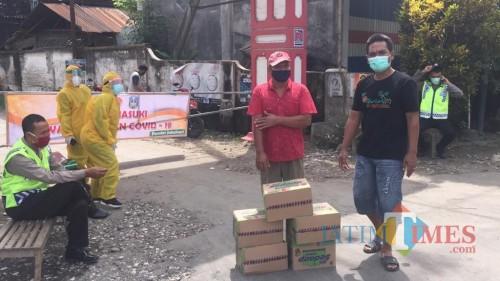 Karena tak ada kiriman sembako dari pemerintah warga mencari dan mengambil bantuan di pintu gerbang desa yang ditutup (Foto : Istimewa / TulungagungTIMES)