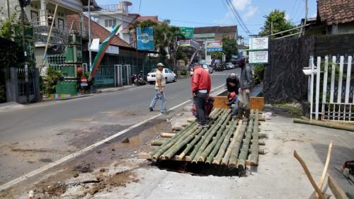 Petugas sedang memasang bambu pengganti jalan di Jalan Semeru Kota Batu. (Foto: istimewa)