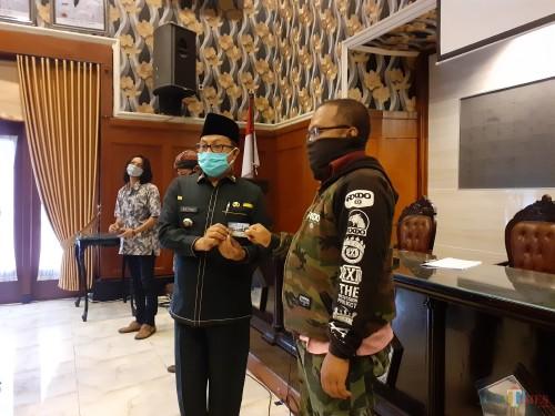 Wali Kota Malang Sutiaji (berkopyah) saat menyerahkan kartu bantuan sosial secara simbolis kepada warga terdampak Covid-19, Rabu (29/4). (Arifina Cahyanti Firdausi/MalangTIMES).