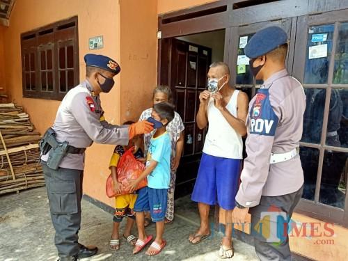 Anggota B Pelopor Satbrimob Polda Jawa Timur, Malang, saat membagikan masker dan sembako kepada warga yang membutuhkan. (Foto : Istimewa)