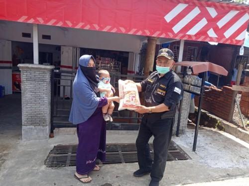Bupati Malang, HM Sanusi saat membagikan sembako kepada salah satu warga di kawasan Malang Timur