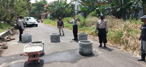 Petugas Polsekta Kedungkandang memasang beton-beton bis dibelakang Gor Ken Arok untuk antisipasi balap liar (Ist)