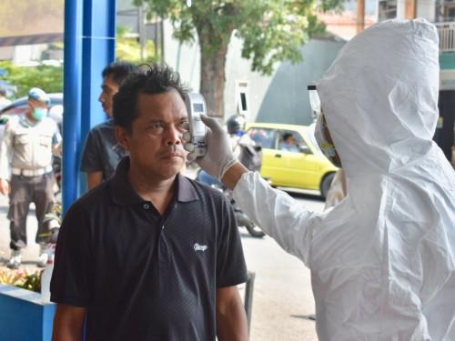 Petugas saat memeriksa suhu tubuh pengendara di pos pemantauan di simpang tiga Pendem, Kecamatan Junrejo. (Foto: istimewa)