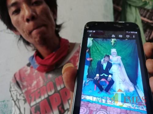 Sandi saat menunjukkan foto pernikahannya dengan Faunatul Fidayah. (Foto : Adi Rosul / JombangTIMES)
