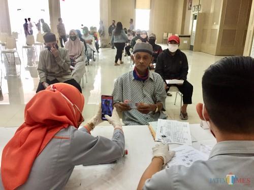 Salah satu warga saat menerima bantuan diGraha Pancasila, Balai Kota Among Tani,Kamis (14/5/2020). (Foto: Irsya Richa/MalangTIMES)