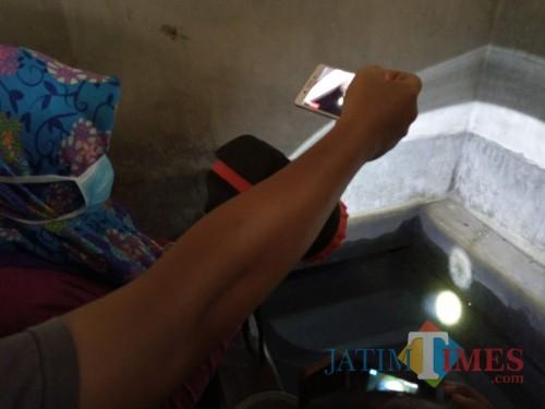 Perugas saat memeriksa kamar mandi yang digunakan jentik nyamuk untuk berkembang biak. (Joko Pramono for Jatim TIMES)