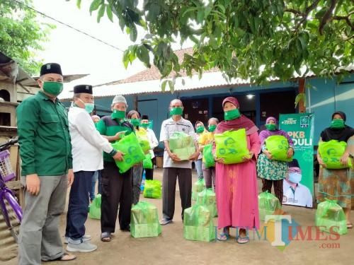 Ketua DPC PKB Kota Blitar Yasin Hermanto menyerahkan simbolik bantuan sembako kepada warga terdampak Covid-19.(Foto : Aunur Rofiq/BlitarTIMES)