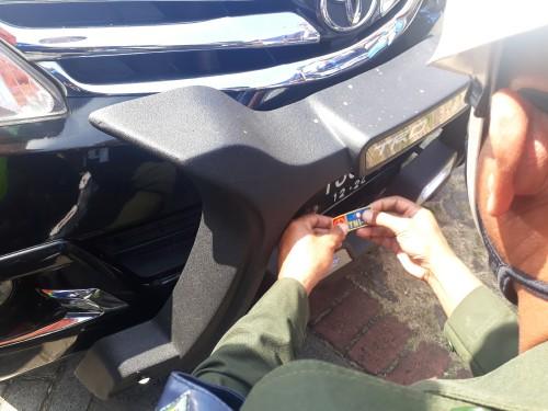 Petugas Polisi Militer (PM) sedang mengambil tindakan mencabut stiker dari kesatuan TNI AU yang berada di plat nomor mobil masyarakat sipil di Check Point Bakpau Telo Lawang, Minggu (17/5/2020). (Foto: Tubagus Achmad/MalangTimes)