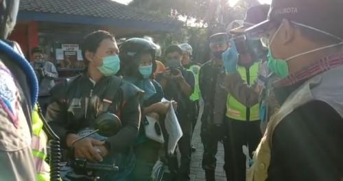 Erna bersama sang suami, warga asal Sidoarjo yang hendak masuk Kota Malang, diminta petugas untuk menunggu di pos check point batas kota di Bale Arjosari. (Ist)