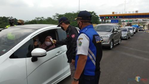 Pemeriksaan suhu tubuh di check point exit Madyopuro Tol Mapan saat pelaksanaan PSBB Malang Raya (Pipit Anggraeni/MalangTIMES).