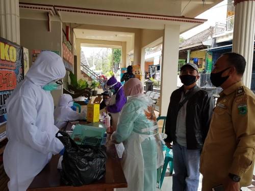 Petugas menggunakan APD saat akan melakukan rapid test kepada pedagang atau pengepul sayur di Desa Giripurno, Kecamatan Bumiaji. (Foto: istimewa)