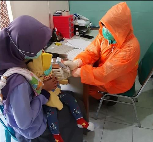 Petugas Kesehatan di Puskesmas Kendalkerep saat memberikan layanan pada balita. (Foto: instagram @puskesmaskendalkerep).