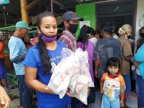 Insiyah menunjukkan tambahan ikan segar yang diterima dalam pencairan BPNT miliknya / Foto : Anang Basso / Tulungagung TIMES