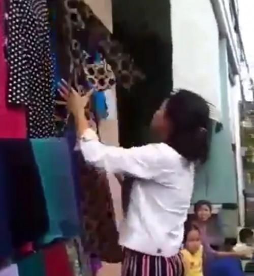 Salah seorang warga yang tengah memilih baju untuk diambil dengan gratis. (Foto: source twitter).