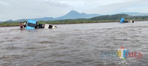 Dua truk yang terseret banjir dikawasan tambang Pandan Arum (Foto : Moch. R. Abdul Fatah / Jatim TIMES)