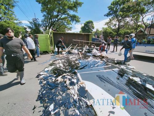 Truk yang terguling dan puluhan lembar kaca yang pecah berserakan di kawasan Arjosari, Kota Malang. (Anggara Sudiongko/Malang TIMES)