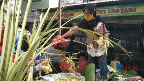 Sulastri, penjual ketupat saat melayani pembeli di pasar Ngempalak (Joko Pramono for Jatim TIMES)