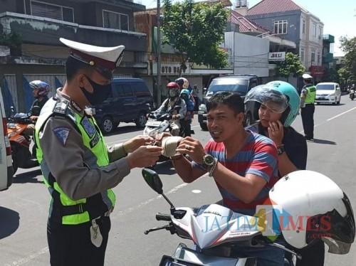 Petugas saat memberikan masker kepada pengendara di Jalan Gajah Mada Kecamatan Batu, Kamis (16/4/2020). (Foto: Irsya Richa/MalangTIMES)