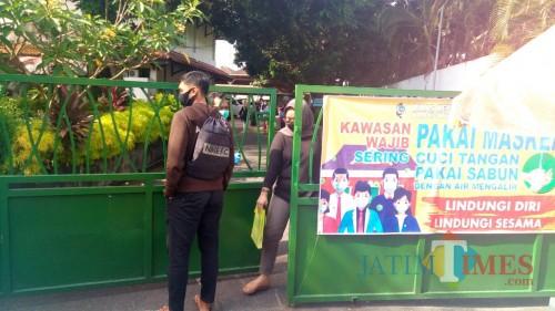 Warga yang mengurus dokumen kependudukan melalui pintu barat Dispendukcapil (Joko Pramono/Jatim TIMES)