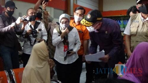 Menko PMK Muhadjir Effendy (bertopi batik ungu) saat meninjau penyaluran BST di Kota Malang, Rabu (3/5). (Ahmad Nur Amin/ MalangTIMES).