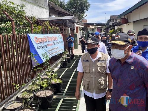 Menko PMK Muhadjir Effendy (bertopi batik ungu) saat melakukan kunjungan ke Kampung Tangguh Semeru RW 05, Kelurahan Purwantoro, Kecamatan Blimbing, Kota Malang, Rabu (3/6).(Arifina Cahyanti Firdausi/MalangTIMES).