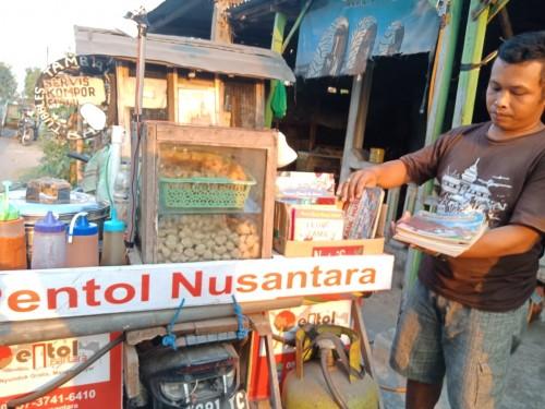 Lutfan menyiapkan buku-buku yang akan dibawanya berjualan pentol keliling. (Foto : Adi Rosul / JombangTIMES)